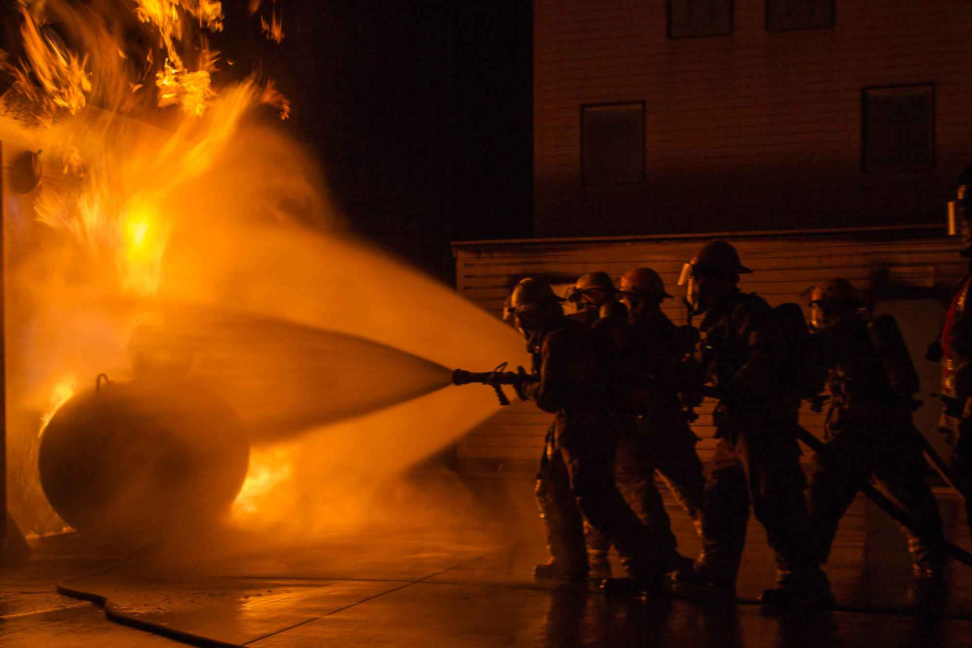 Four student firefighters practice putting out a fire