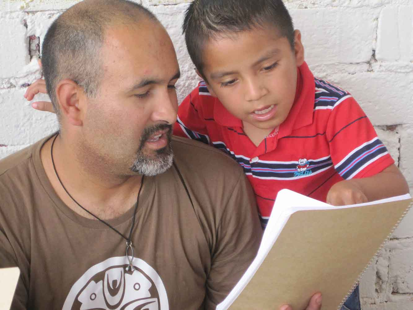A student shows a page from his notebook to his son