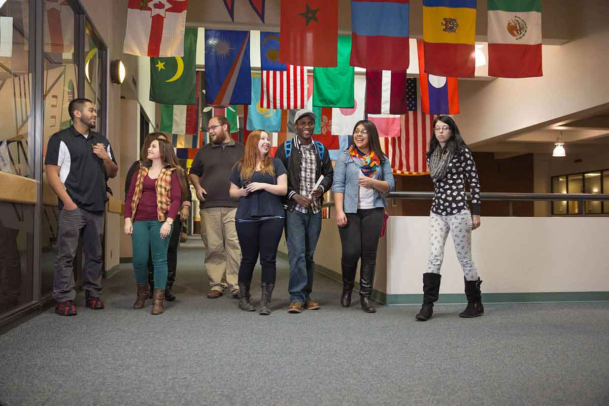 A group of students talking beneath rows of flags from different countries