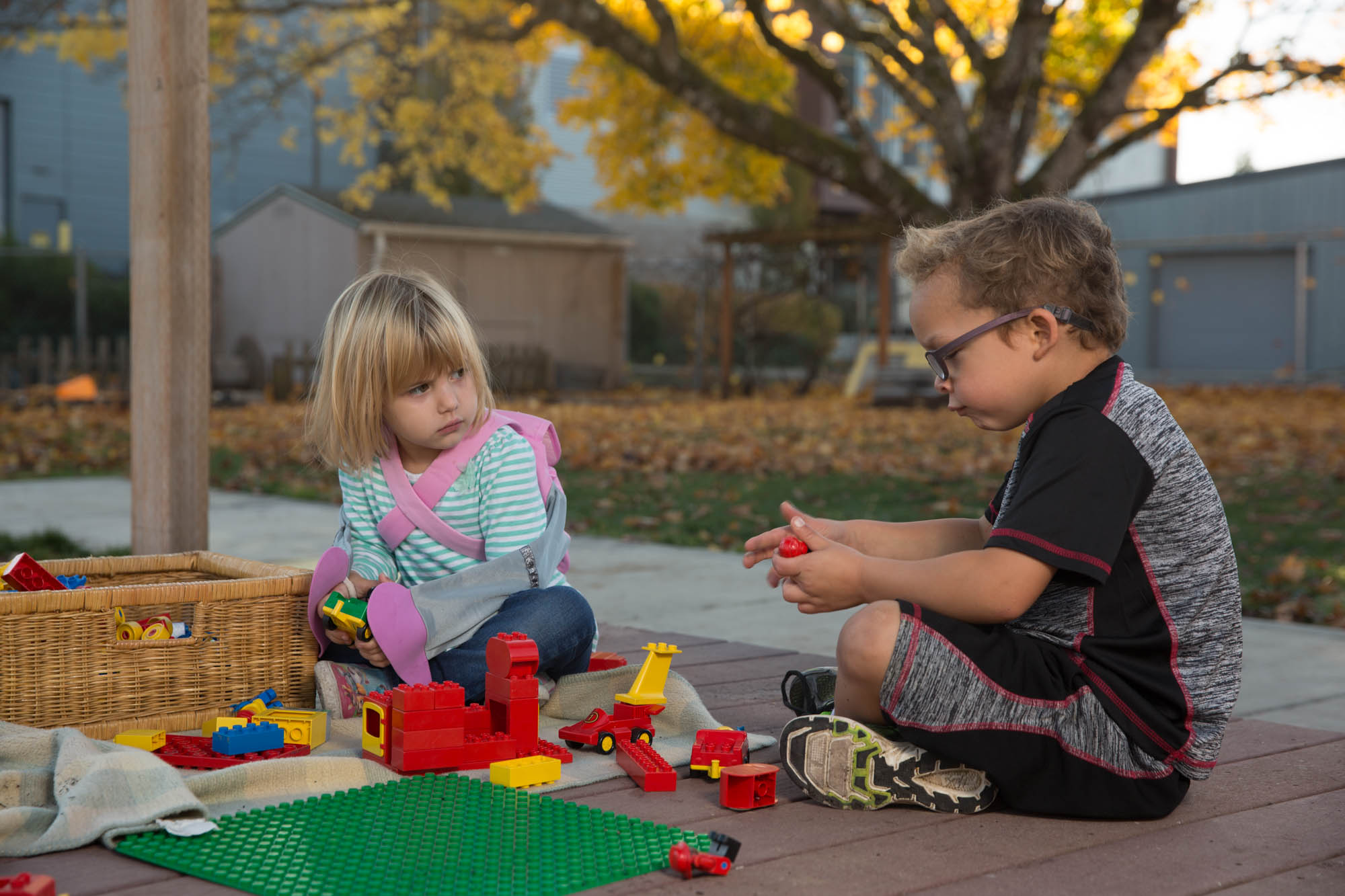 two kids playing with legos outside