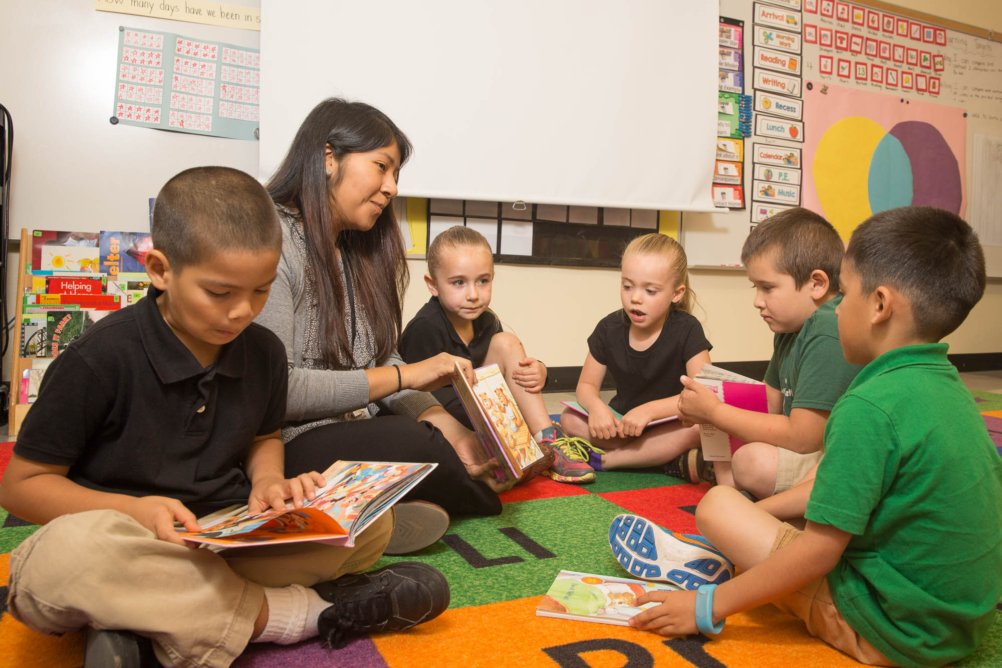 Teacher reading in a classroom to 5 students