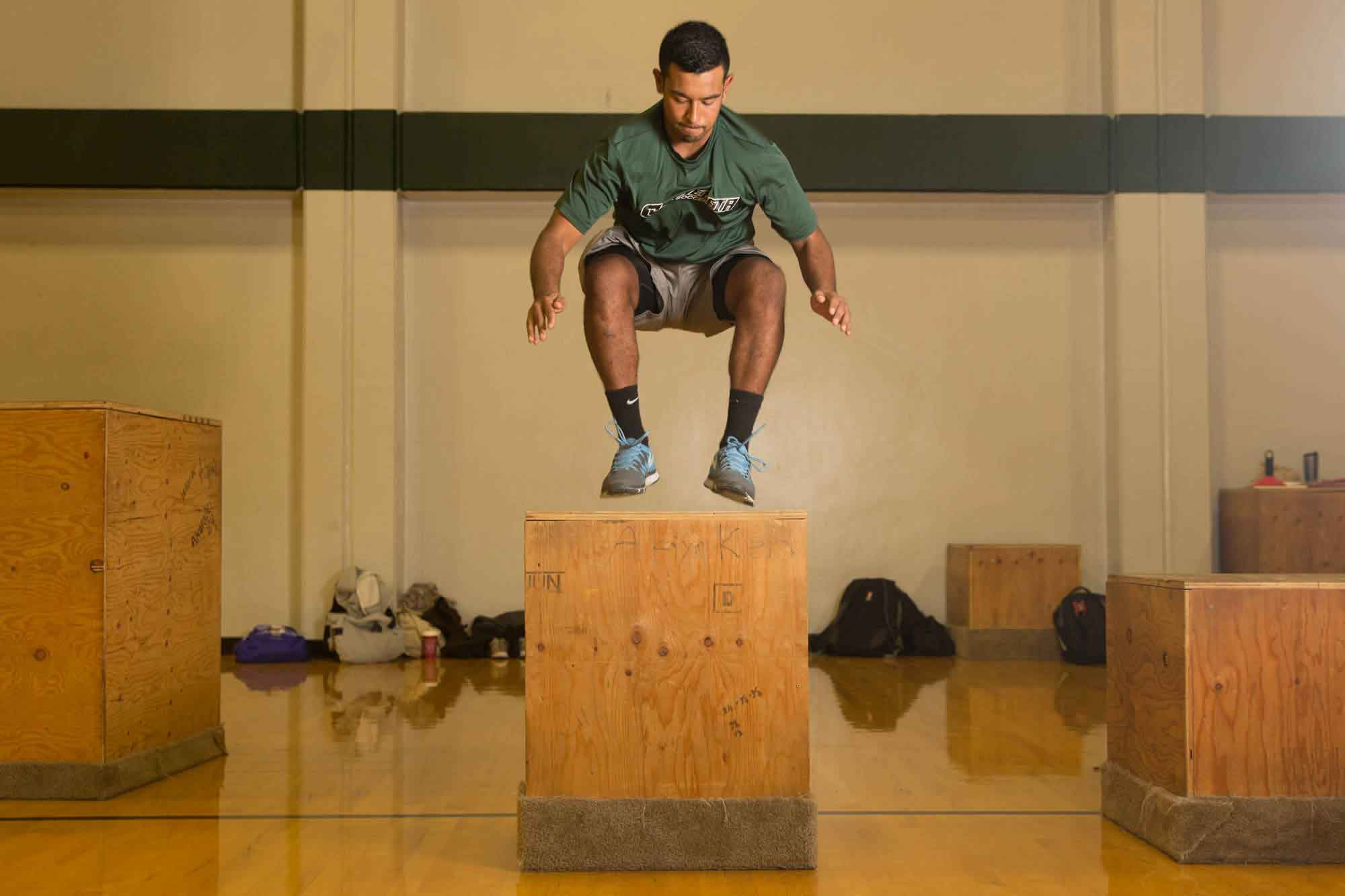 Student jumping onto a large wooden box