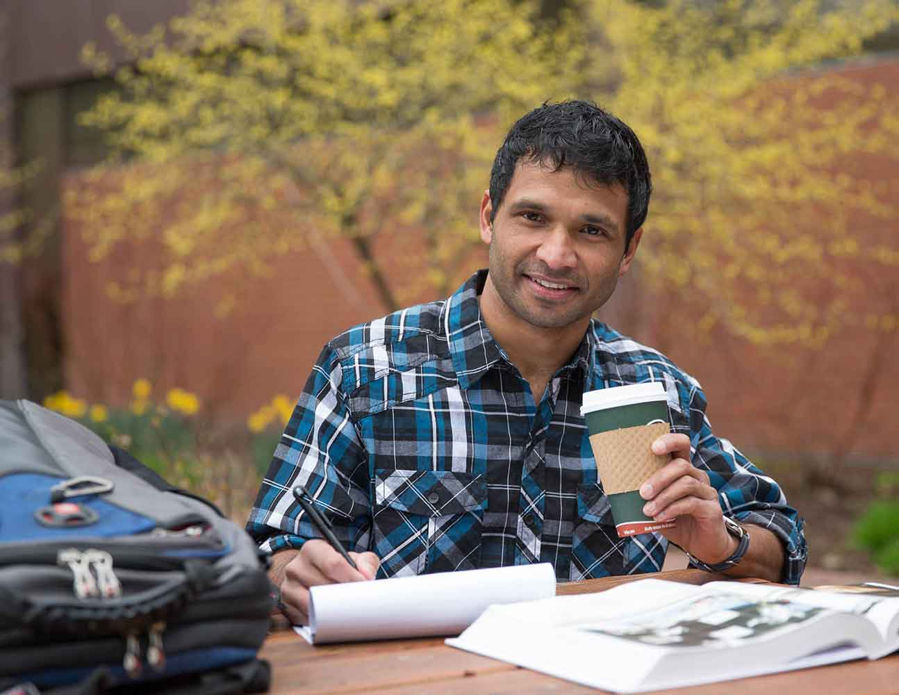 A student writes on a notepad while drinking coffee