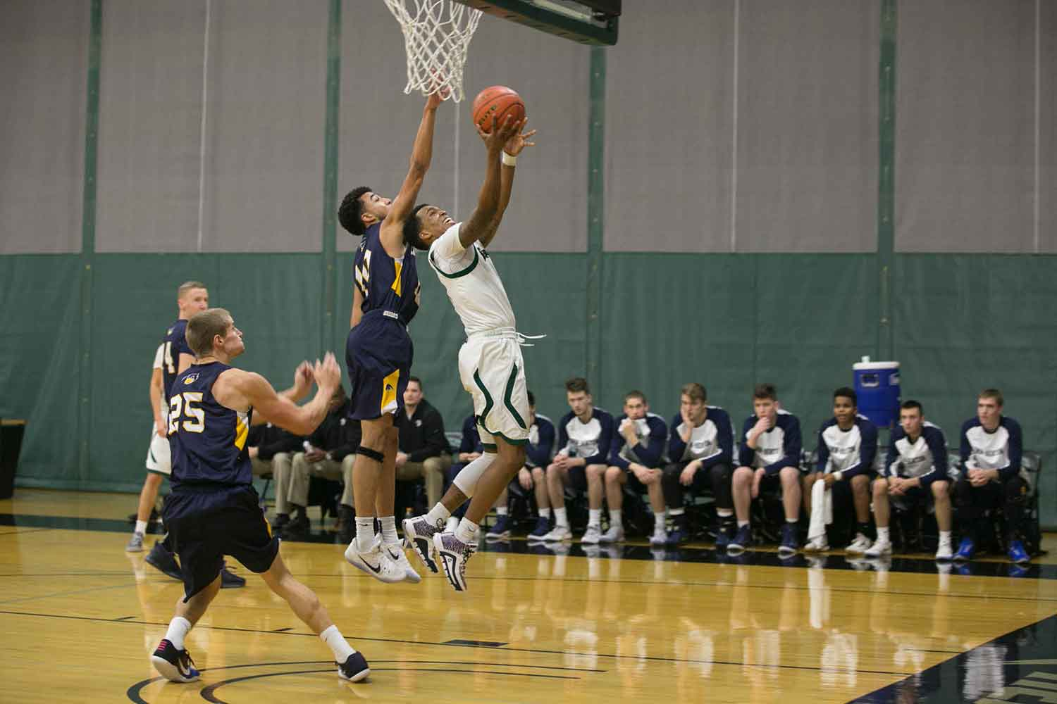 A men's basketball player tries for a basket while the opposing team tries to block