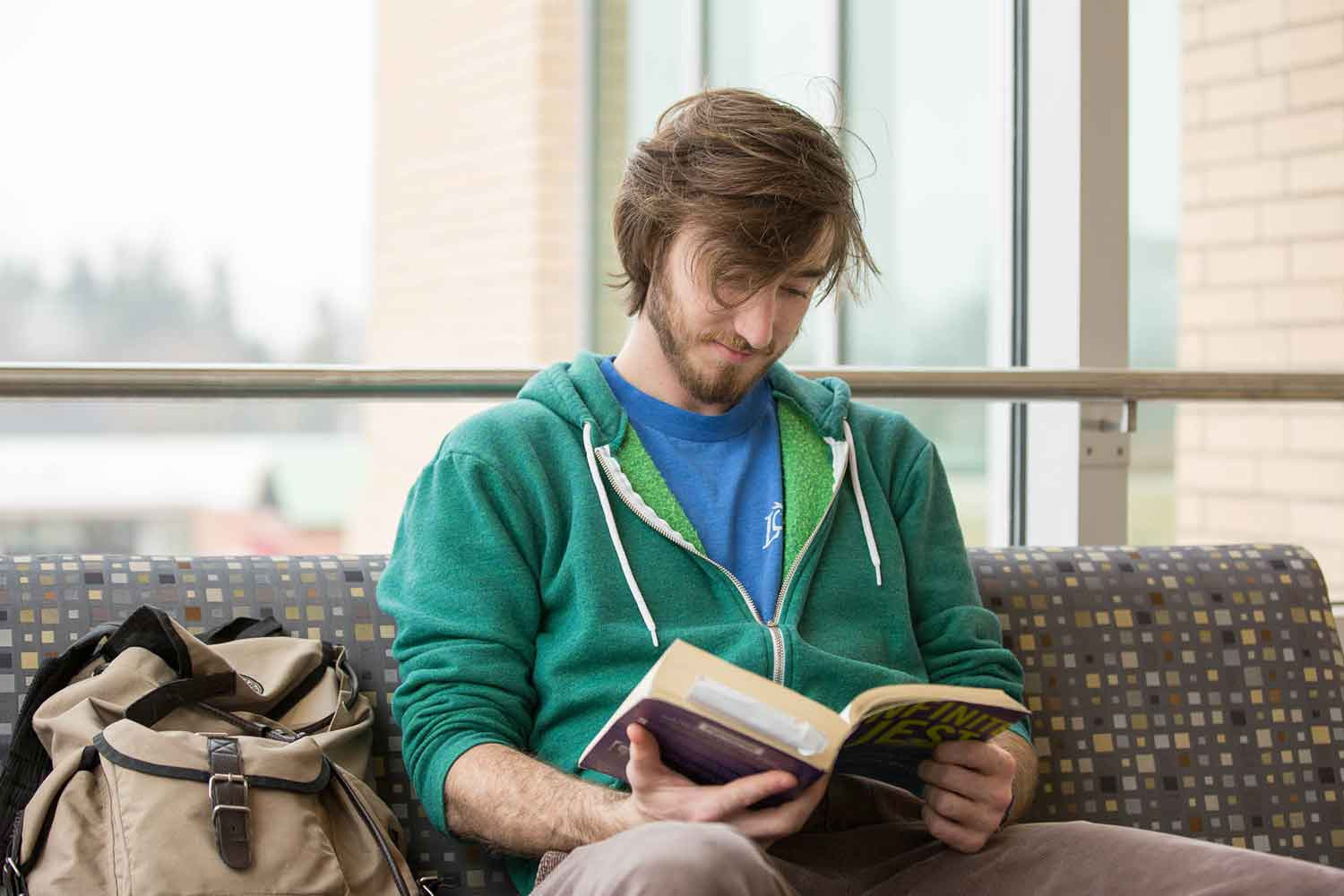 Student reading a book sitting down