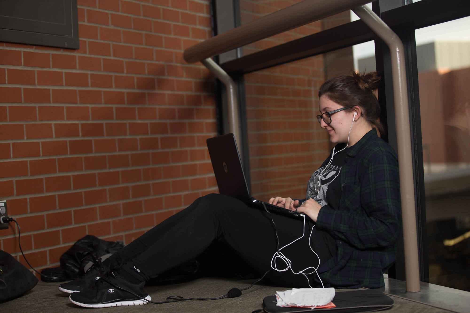 Student sitting down and typing on her laptop