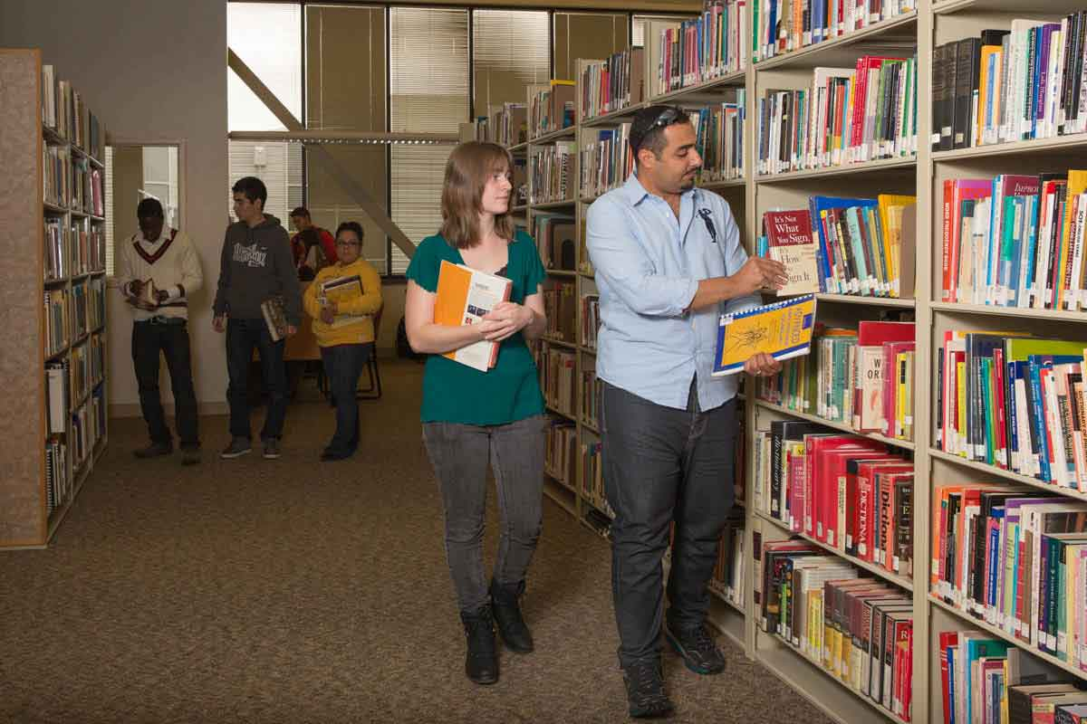 Students standing in the next the stacks of books