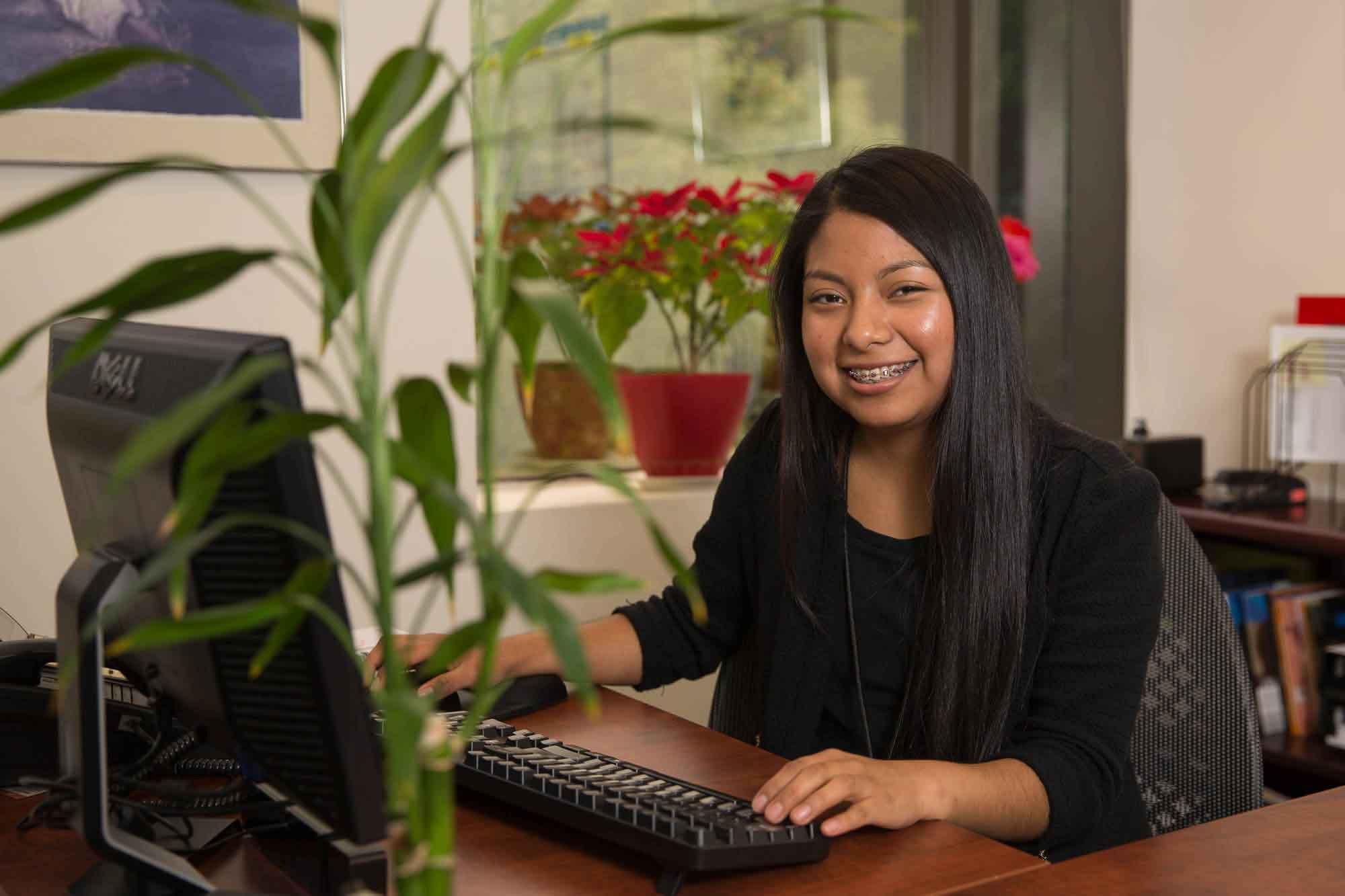 A woman works in an office with a pot of flowers in the background