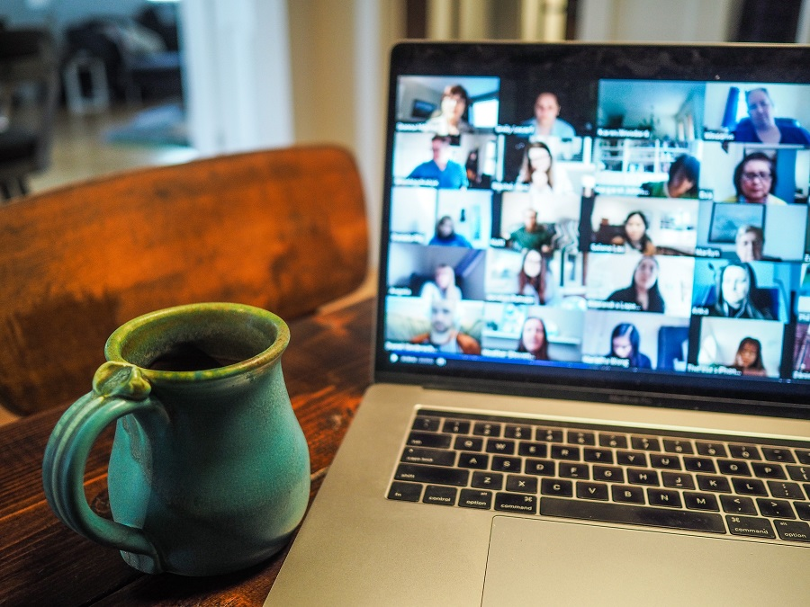 A coffee mug next to a laptop showing a virtual group meeting